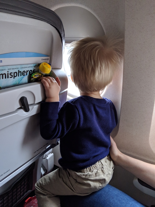 Little boy looking out plane window